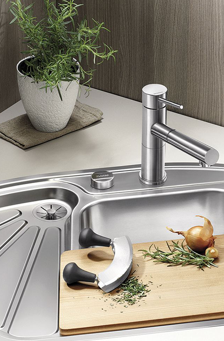 in the kitchen there is a stainless steel sink with 3 different compartments